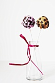 Two lollipops with heart decorations in a vase