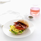A bread roll topped with smoked bacon and scrambled egg
