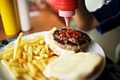 Squeezing ketchup onto a hamburger bun
