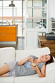 Woman with slice on cake lying on sofa