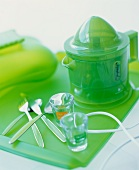 An electric citrus press on a green glass tray