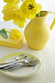 Yellow tulips in a jug with cutlery on a plate