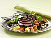 Roasted ostrich steaks with root vegetables