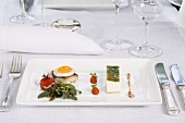 Tomato and rocket mouse, quail's eggs and mackerel with a herb salad in a restaurant