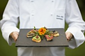 A chef serving a plate of various crostinis