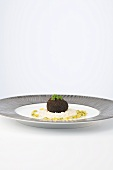 Baked egg with an olive coating with cheese risotto and yellow beet vinaigrette