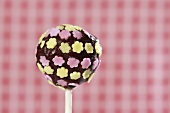 A cake pop, chilled and decorated with chocolate and sugar flowers