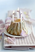 A mini Bundt cake with rose petal icing and candles