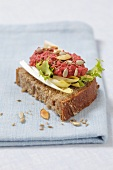 Wholemeal bread topped with chicory, beetroot paste, sunflower seeds and pumpkin seeds