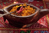 Curry powder and chilli peppers in a wooden bowl
