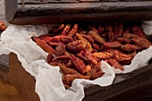 Dried chilli peppers on paper in a wooden crate