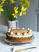 A cake in a shallow glass bowl and a vase of daffodils