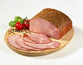 Sliced pepper ham on a wooden plate