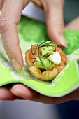 A hand holding a napkin with a salmon and avocado tartlet