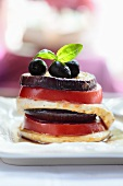 An aubergine, tomato and mozzarella tower with olives