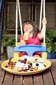 Pancakes with forest fruits on a wooden table and a girl in the background on a swing