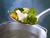 Mixed vegetables in a ladle over a saucepan