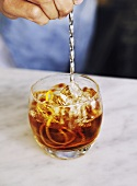 An Old Fashioned being stirred
