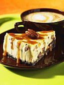 A slice of caramel cheesecake with pecan nuts and a cafe latte