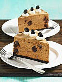 Two slices of mocca cheesecake with chocolate pieces