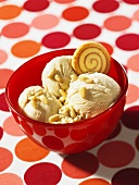 Honey ice cream with pine nuts in a red bowl on a polka dot