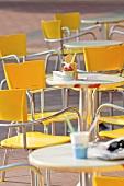 Stühle und Tische vor einer Eisdiele
