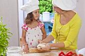 Mutter und Tochter kneten Pizzateig