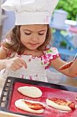 Kleines Mädchen bestreicht Pizza mit Tomatensauce