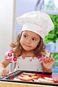 Kleines Mädchen belegt ungebackene Pizzen