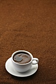 A cup of black coffee on coffee powder