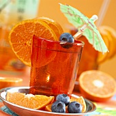 Clementine juice with cocktail umbrellas and garnished with blue berries