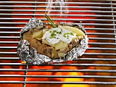 Baked potatoes in aluminum foil on the grill