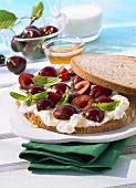 Open faced sandwich with cream cheese, honey and cherries