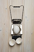 Egg slicer with raw egg and eggshells