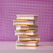 A stack of cream-filled waffers in front of a pink background