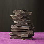 Pieces of chocolate stacked on a pink colored surface