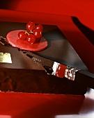 Schokoladentorte mit roten Johannisbeeren anschneiden