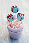 Blue gift-shaped cake pops with red sugar bows in a cup of colourful sugar strands