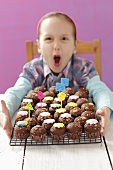A girl with a wire rack of mini chocolate cupcakes