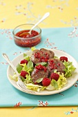 Turkey liver with raspberry sauce on a mixed leaf salad