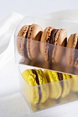 Chocolate macaroons and yellow macaroons in a plastic box