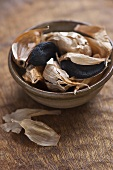 Black garlic, semi peeled, in a ceramic bowl