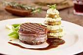 Beef medallions wrapped in bacon with a pear and mashed potato tower