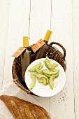 Slices of avocado on a plate with bottle of salad dressing and white bread