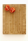 Two tomato halves on a chopping board