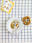 Remains of food on a plate, a pretzel and a child's drawing