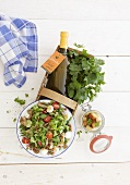 Vegetable salad, bottles of dressing and parsley in a basket
