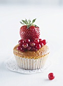 A muffin topped with redcurrants and strawberries