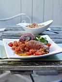 Crispy pork rolls with raw ham on tomato ragout