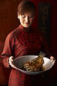 A woman serving wok-fried carp (China)